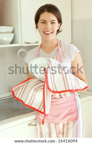 beautiful smiling girl in the kitchen with a plate - stock photo