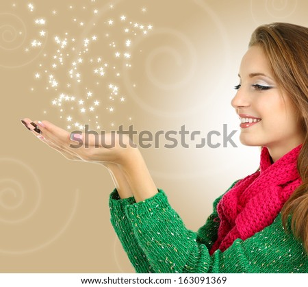 Beautiful smiling girl in warm knit scarf on bright background