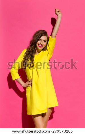 Beautiful smiling girl in yellow mini dress posing with arm raised. Three quarter length studio shot on pink background. - stock photo