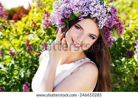 Beautiful smiling girl is wearing beautiful wreath of lilac flowers, spring time - stock photo