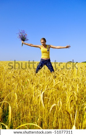Beautiful smiling girl jumps in golden field
