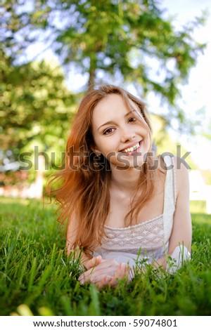 Beautiful smiling girl lies on green lawn. - stock photo
