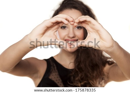 beautiful smiling girl looking through her ??fingers heart frame - stock photo