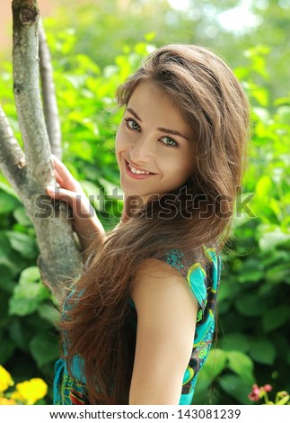 Beautiful smiling girl near the tree looking on summer background - stock photo