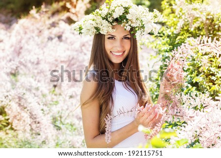 Beautiful smiling girl on the nature in wreath of white flowers - stock photo