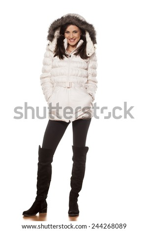 beautiful smiling girl posing with winter coat and a fur hood - stock photo
