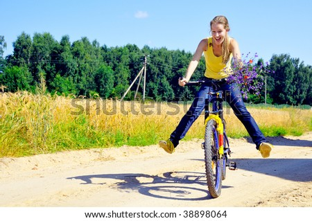 Beautiful smiling girl rides bicycle on village road