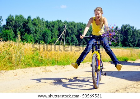 Beautiful smiling girl rides bicycle on village road - stock photo