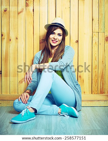 Beautiful smiling girl sitting against wooden background on a floor. Youth teen style portrait. - stock photo
