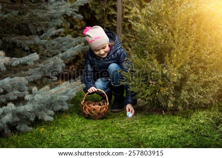 Beautiful smiling girl taking Easter egg form under the bush a backyard - stock photo