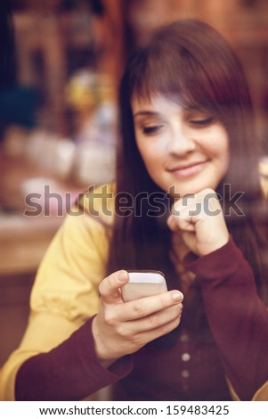 Beautiful smiling girl using smart phone in a cafe. The photo was taken through the window - stock photo