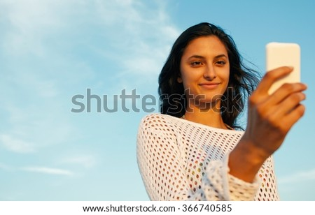 Beautiful smiling girl using smart phone on a sunny day - stock photo