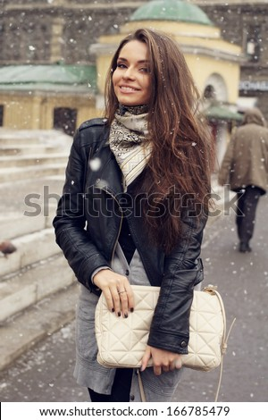 Beautiful smiling girl walking down street in the snow - stock photo