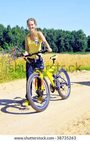 Beautiful smiling girl walks with bicycle on village road