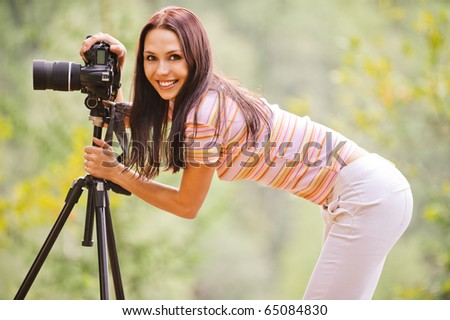 Beautiful smiling girl with camera on nature. - stock photo
