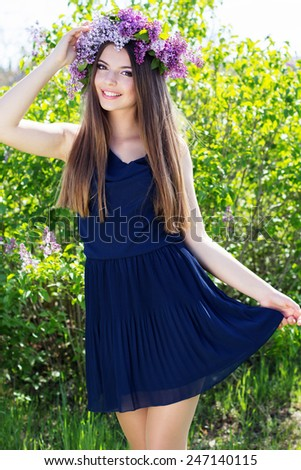 Beautiful smiling girl with fashion makeup is wearing dress and beautiful wreath of lilac flowers - stock photo