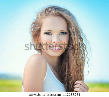 Beautiful smiling girl with long curly hair outdoor - stock photo