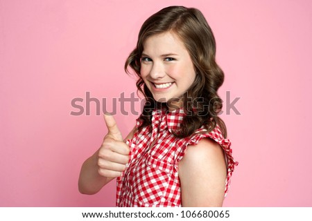 Beautiful smiling girl with ok gesture,side view