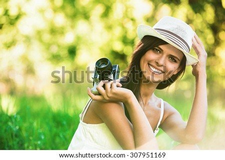 Beautiful smiling girl with old camera on nature - stock photo
