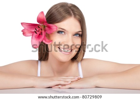 beautiful smiling girl with pink lily in hair, isolated on white background