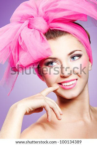 Beautiful smiling girl with pink makeup and bow on head