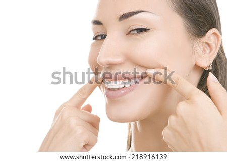 Beautiful smiling girl with retainer for teeth pointing at her smile isolated on white background - stock photo