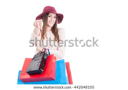 Beautiful smiling girl with shopping bags pointing finger at the camera isolated on white background with copyspace - stock photo