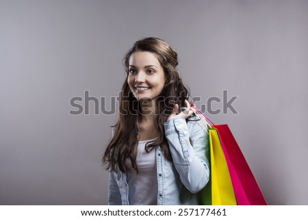 Beautiful smiling girl with shopping bags. Studio shot on gray background.