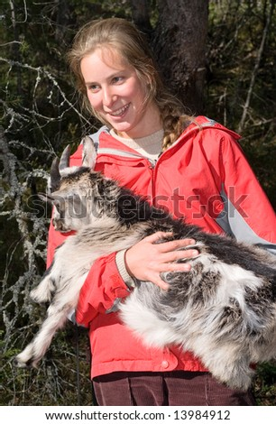 Beautiful smiling girl with young goat in her hands