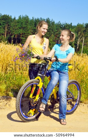 Beautiful smiling girls rest from ride bicycle on village road