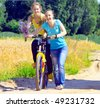 Beautiful smiling girls walk with bicycle on village road - stock photo