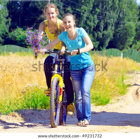 Beautiful smiling girls walk with bicycle on village road