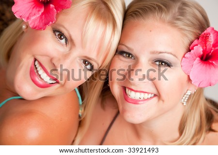 Beautiful Smiling Girls with Hibiscus Flowers in Their Hair. - stock photo