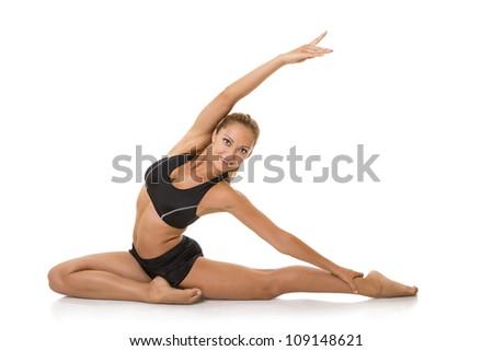 Beautiful smiling gymnast doing stretching exercises, isolated on white. - stock photo