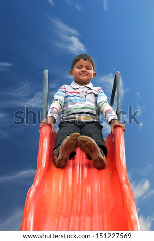 Beautiful smiling ( happy ) indian boy(kid) on slider in a summer day. This boy's photo with sky in the background & clipping path shows summer time playground with a schoolboy playing on a slider  - stock photo