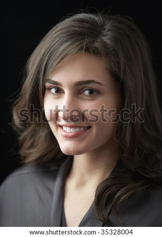 Beautiful smiling happy young woman on black - stock photo