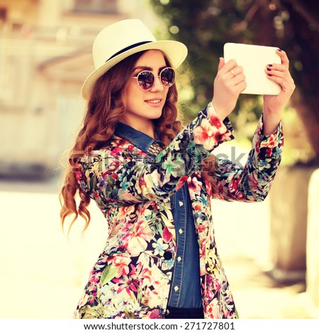 Beautiful smiling hipster woman wear vintage sunglasses, jeans shirt, white hat and jacket take a picture of herself with digital tablet. Toned in warm colors. Outdoors shot, lifestyle - stock photo