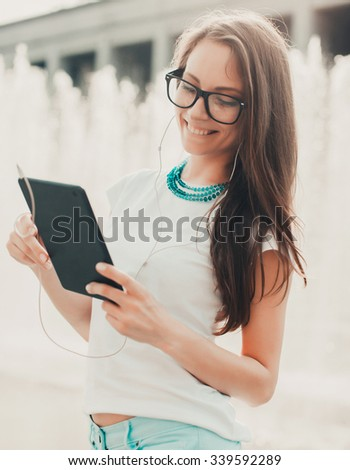 Beautiful smiling hipster woman wear vintage sunglasses, jeans shirt, white hat and jacket take a picture of herself with digital tablet. Selfie style. Toned in warm colors. Outdoors shot, lifestyle