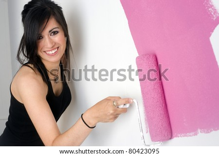 Beautiful Smiling Housewife Paints a Pink Stripe of Paint With Roller - stock photo