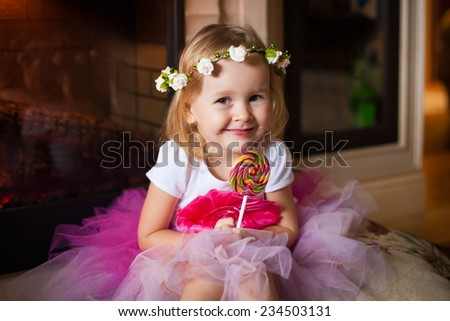 beautiful  smiling  little blonde girl  in pink skirt with lollipop on home background birthday fresh trendy summer spring joy happy look cute studio impressions lady