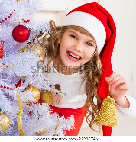 beautiful  smiling  little blonde girl near the christmas tree with tree toy - stock photo
