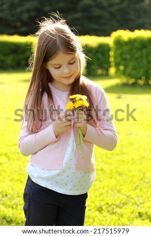 Beautiful smiling little girl holding a bouquet of yellow daisies in the park