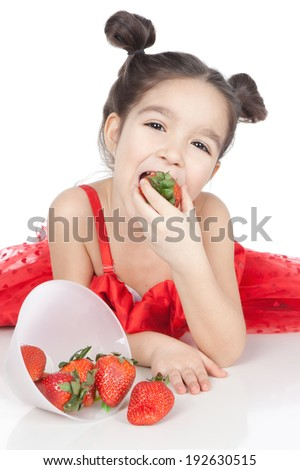 Beautiful smiling little girl in red dress with fresh strawberries over white background - stock photo