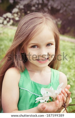 Beautiful smiling little girl in the summer garden - stock photo