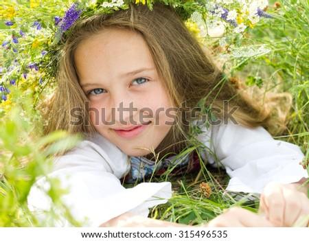 Beautiful smiling  little girl in wreath of flowers  in meadow - stock photo