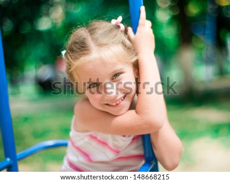 beautiful smiling little girl on a playground - stock photo