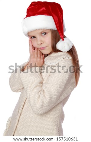 Beautiful smiling little girl wearing Santa hat