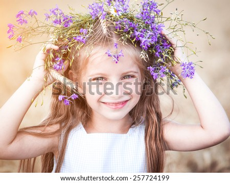 beautiful smiling little girl with a wreath on his head in a field of wheat close-up - stock photo