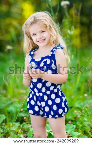 Beautiful smiling little girl with long blond curly hair and flower in her hands. Outdoor full-length portrait in summer park on bright sunny day. Child in green grass field. - stock photo