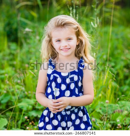 Beautiful smiling little girl with long blond curly hair and flower in her hands. Outdoor portrait in summer park on bright sunny day. Child in green grass field. - stock photo